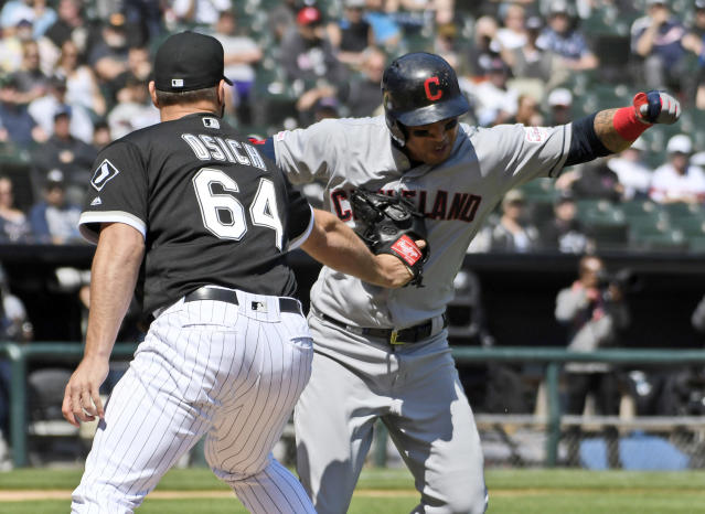 Chicago White Sox relief pitcher Josh Osich (64) tags out Cleveland Indians' Leonys Martin (2) as he runs to first base during the fifth inning of a baseball game, Tuesday, May 14, 2019, in Chicago. (AP Photo/David Banks)