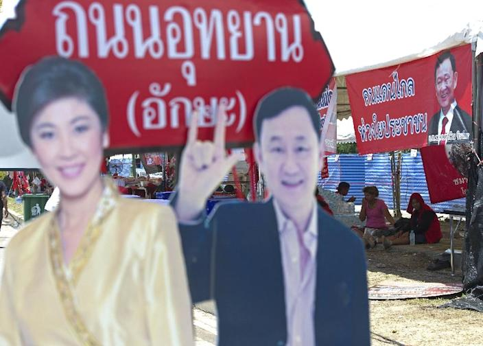 """Pro-government """"Red shirt"""" protesters (R) sit next to portraits of ousted Thai Prime Minister Yingluck and Thaksin Shinawatra during a rally on the outskirts of Bangkok on May 21, 2014 (AFP Photo/Pornchai Kittiwongsakul)"""