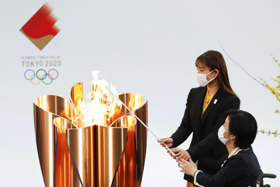 Japanese actress Satomi Ishihara, second from right, and Paralympian Aki Taguchi light the celebration cauldron on the first day of the Tokyo 2020 Olympic torch relay in Naraha, Fukushima prefecture, northeastern Japan, Thursday, March 25, 2021. The torch relay for the postponed Tokyo Olympics began its 121-day journey across Japan on Thursday and is headed toward the opening ceremony in Tokyo on July 23. (Kim Kyung-Hoon/Pool Photo via AP)