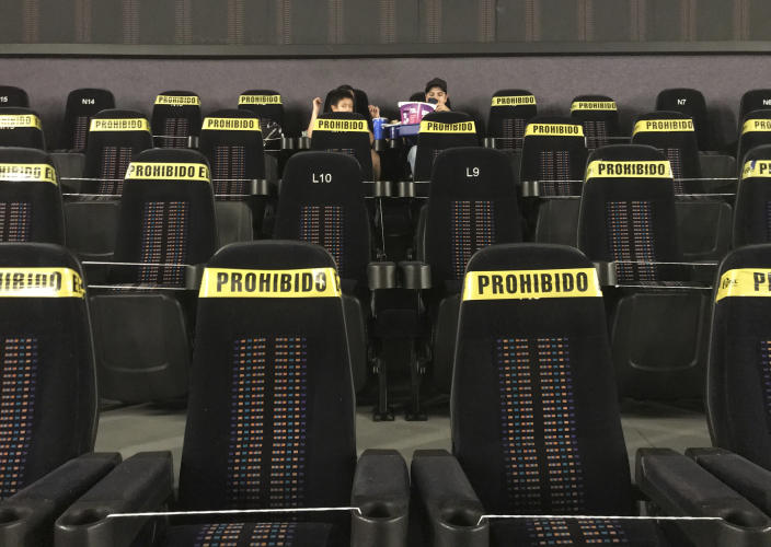 """A couple of youths wait for the start of a movie, in an almost empty movie house with most of the seating blocked with yellow tape that reads in Spanish """"Prohibited,"""" to help curb the spread of the new coronavirus, in Mexico City, Tuesday, April 27, 2021. (AP Photo/Marco Ugarte)"""