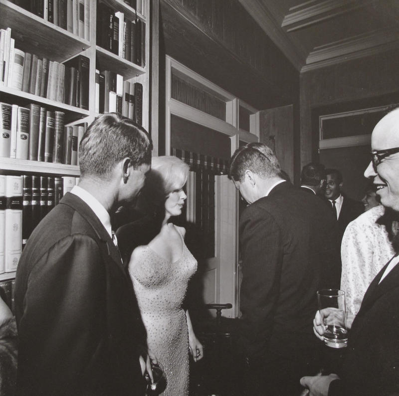 """This photo provided by Bonhams auction house, by former White House photographer Cecil Stoughton, shows Marilyn Monroe with President John F. Kennedy, center, and Robert Kennedy, left, at a Democratic fundraiser on May 19, 1962 at a home in New York City. Monroe had come straight from Madison Square Garden where she had sung """"Happy Birthday"""" to the president.  It is one of a trove of JFK photos being offered by Stoughton's estate at Bonhams auction house in New York, Thursday, Dec. 9, 2010. (AP Photo/Bonhams, Cecil Stoughton) NO SALES"""