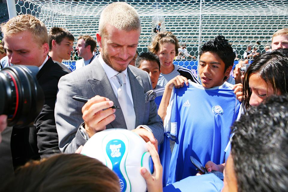 David Beckham poses signs autographs for young fans following to a press conference introducing him as the newest member of the Los Angeles Galaxy on July 13, 2007 at the Home Depot Center in Carson, CA.