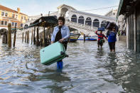 People carry their luggage as they wade through water during a high tide of 4.72 feet, near the Rialto Bridge in Venice on Monday. (AP)