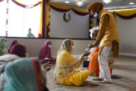 Kraa prashaad is handed out during Vaisakhi celebrations at Guru Nanak Darbar of Long Island, Tuesday, April 13, 2021 in Hicksville, N.Y. Sikhs across the United States are holding toned-down Vaisakhi celebrations this week, joining people of other faiths in observing major holidays cautiously this spring as COVID-19 keeps an uneven hold on the country. (AP Photo/Jason DeCrow)