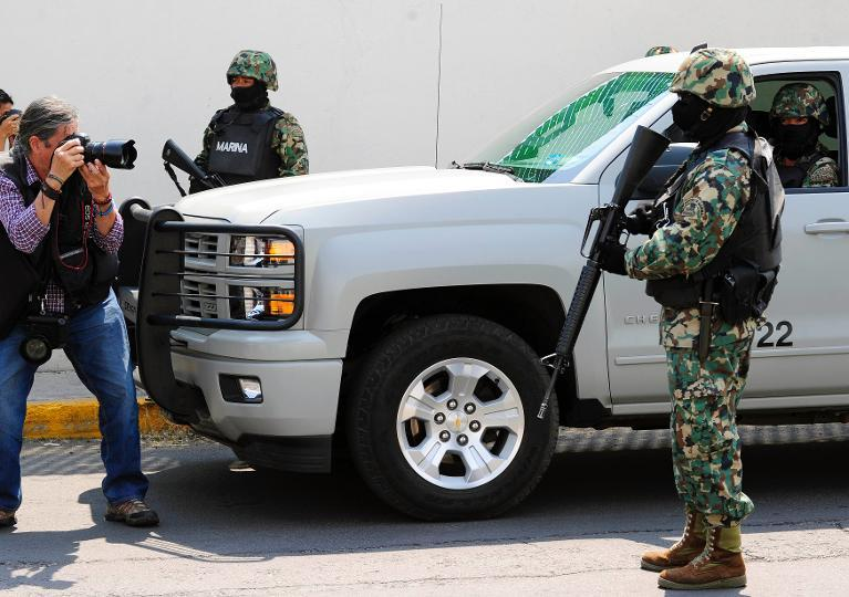 "Members of the Mexican Navy stand guard during an operation to present Mexican drug trafficker Joaquin Guzman Loera aka ""el Chapo Guzman"" to the press, on February 22, 2014 in Mexico City"