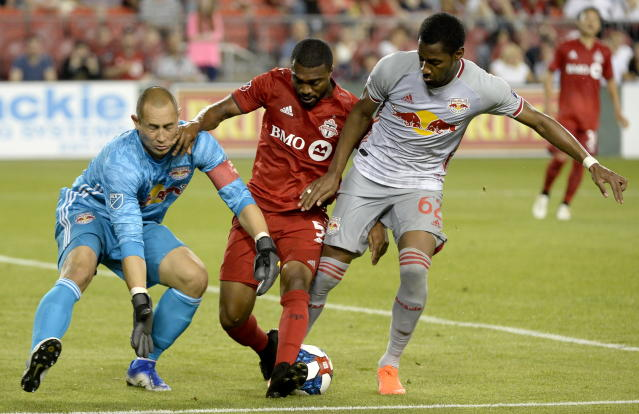 New York Red Bulls defender Michael Murillo (62) fails to stop Toronto FC defender Ashtone Morgan (5) from taking the ball away from Red Bulls goalkeeper Luis Robles (31) dduring the second half of an MLS soccer match Wednesday, July 17, 2019, in Toronto. Morgan went on to score. (Nathan Denette/The Canadian Press via AP)