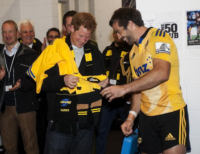 Britain's Prince Harry (L) is presented with a Hurricanes outfit for Princess Charlotte by Hurricanes' captain Conrad Smith during the Super 15 Rugby Union match against RSA Sharks in Wellington on May 9, 2015 (AFP Photo/Dave Lintott Photography)