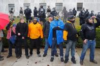 Members of the Proud Boys stand in front of police at a rally in support of U.S. President Donald Trump at the Oregon State Capitol in Salem