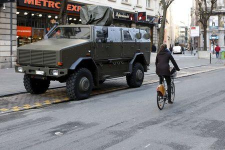 A cyclist rides past a military armoured vehicle in central Brussels, December 31, 2015. REUTERS/Francois Lenoir