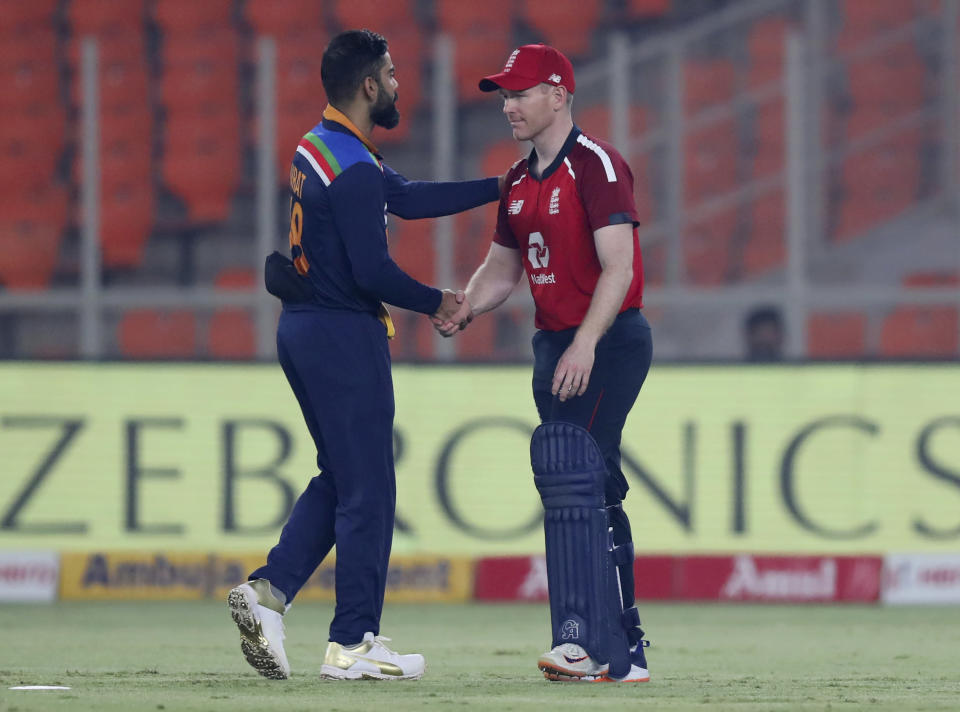 India's captain Virat Kohli, left, shakes hands with England's captain Eoin Morgan after India won the fifth Twenty20 cricket match between India and England at Narendra Modi Stadium in Ahmedabad, India, Saturday, March 20, 2021. (AP Photo/Ajit Solanki)