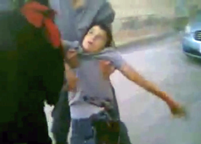 This image made from amateur video released by Shaam News Network and accessed Friday, April 27, 2012 purports to show people carrying a boy in Daraa, Syria. (AP Photo/Shaam News Network via AP video) TV OUT, THE ASSOCIATED PRESS CANNOT INDEPENDENTLY VERIFY THE CONTENT, DATE, LOCATION OR AUTHENTICITY OF THIS MATERIAL