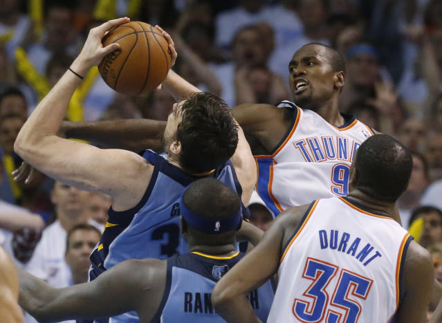 Memphis Grizzlies center Marc Gasol, back left, shoots as Oklahoma City Thunder forward Serge Ibaka (9) defends during the fourth quarter of Game 5 of an opening-round NBA basketball playoff series in Oklahoma City, Tuesday, April 29, 2014. Memphis won 100-99 in overtime. (AP Photo)
