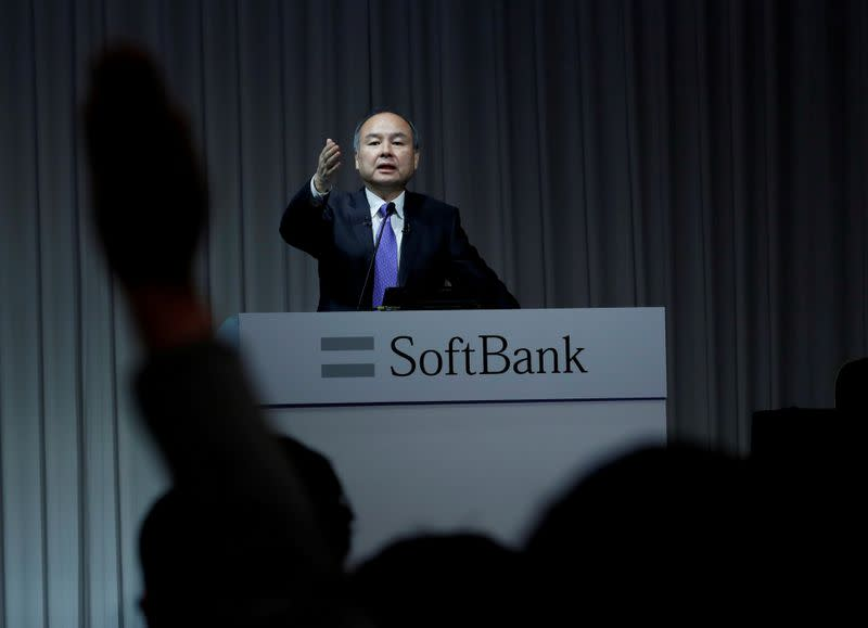 FILE PHOTO: A journalist raises her hand to ask a question to Japan's SoftBank Group Corp Chief Executive Masayoshi Son during a news conference in Tokyo