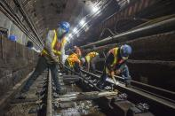 This June 15, 2019 photo provided by the Metropolitan Transportation Authority shows workers during the L Project subway tunnel rehabilitation, in New York. Eight years ago Thursday, Oct. 29, 2020, Superstorm Sandy pushed the Hudson River over its banks, sending 8 feet of water onto underground tracks and leaving the main waiting room unusable for months. New York's Metropolitan Transportation Authority, which serves several million riders daily on subways, trains and buses, had to repair damage to more than a dozen bridges and tunnels, many pre-dating World War II, caused by tens of millions of gallons of saltwater. (Trent Reeves/Metropolitan Transportation Authority via AP)
