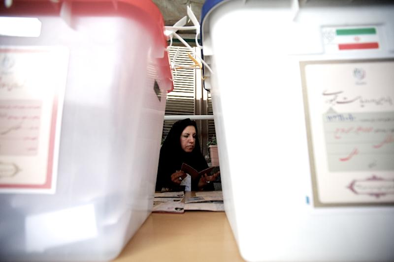 An Iranian woman shows her passport as she votes in the first round of the presidential election at a polling station in Tehran in 2013 (AFP Photo/Behrouz Mehri)