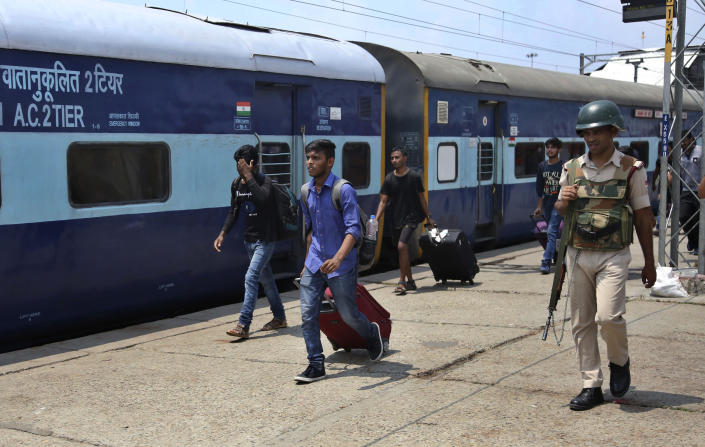 """National Institute of Technology (NIT) students who left Srinagar, Kashmir's main city arrive to board a train to leave for their respective homes from a railway station in Jammu, India, Sunday, Aug. 4, 2019. Thousands of Indian students and visitors were fleeing Indian-controlled Kashmir over the weekend after the government ordered tourists and Hindu pilgrims visiting a Himalayan cave shrine """"to curtail their stay"""" in the disputed territory, citing security concerns. (AP Photo/Channi Anand)"""