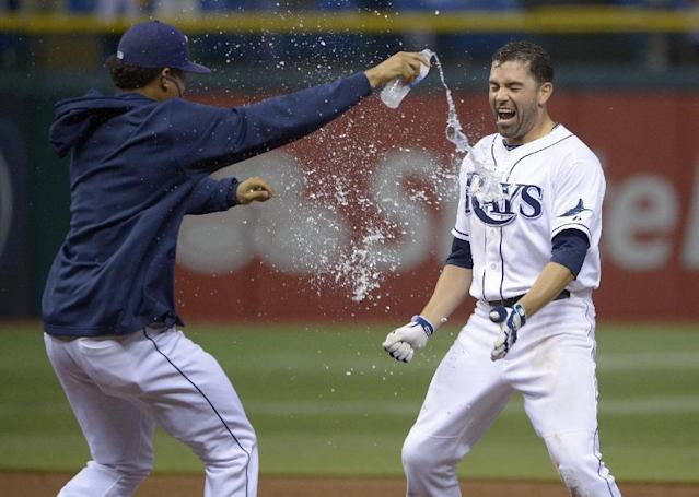 Tampa Bay Rays' David DeJesus, right, is congratulated by teammate Chris Archer after hitting the game-winning single for a 5-4 win over the Baltimore Orioles in 18 innings during a baseball game in St. Petersburg, Fla., Saturday, Sept. 21, 2013.(AP Photo/Phelan M. Ebenhack)