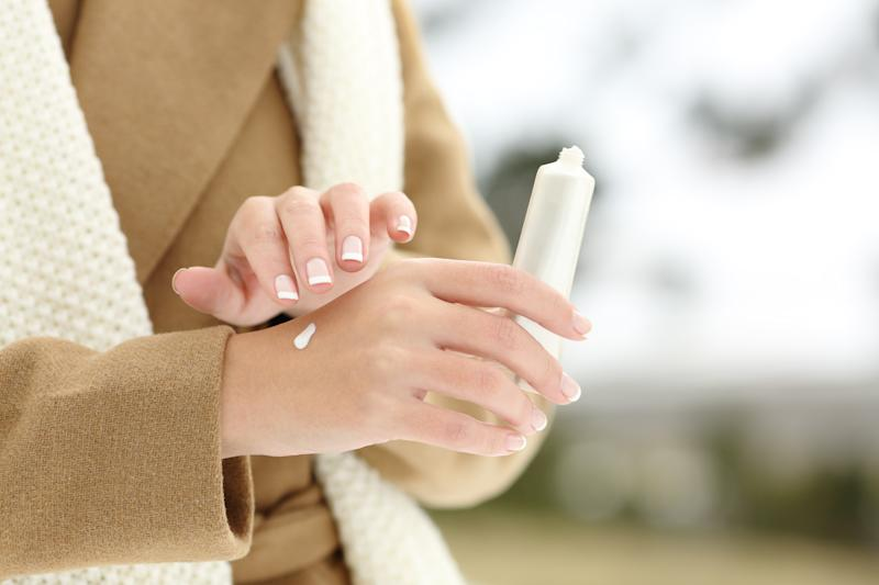 Close up of a woman hand hydrating skin applying cream in winter