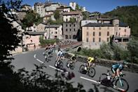 In the lead: Adam Yates (2nd-R) speeding through the village of Saint-Sernin-sur-Rance as he protected his yellow jersey