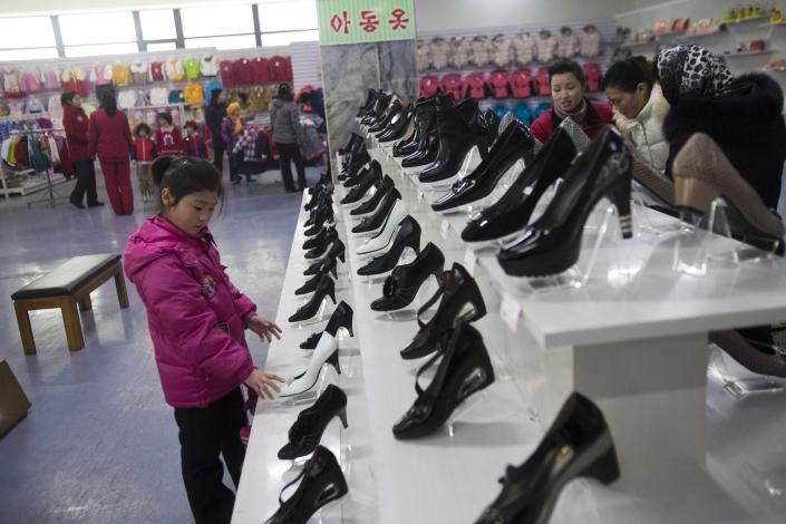 In this Thursday, Jan. 19, 2012 photo, a girl looks at shoes for women at the Kwangbok Area shopping center in Pyongyang, North Korea. A new culture of commerce is springing up, with China as its inspiration and source. The new consumerism is part of a campaign launched three years ago to build up the economy, and so the image of new leader Kim Jong Un. (AP Photo/David Guttenfelder)