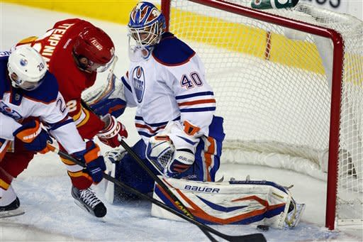 Edmonton Oilers goalie Devan Dubnyk, right, stops a shot from Calgary Flames' Lee Stempniak, center, during the third period of an NHL hockey game in Calgary, Alberta, Saturday, Jan. 26, 2013. The Flames won 4-3. (AP Photo/The Canadian Press, Jeff McIntosh)