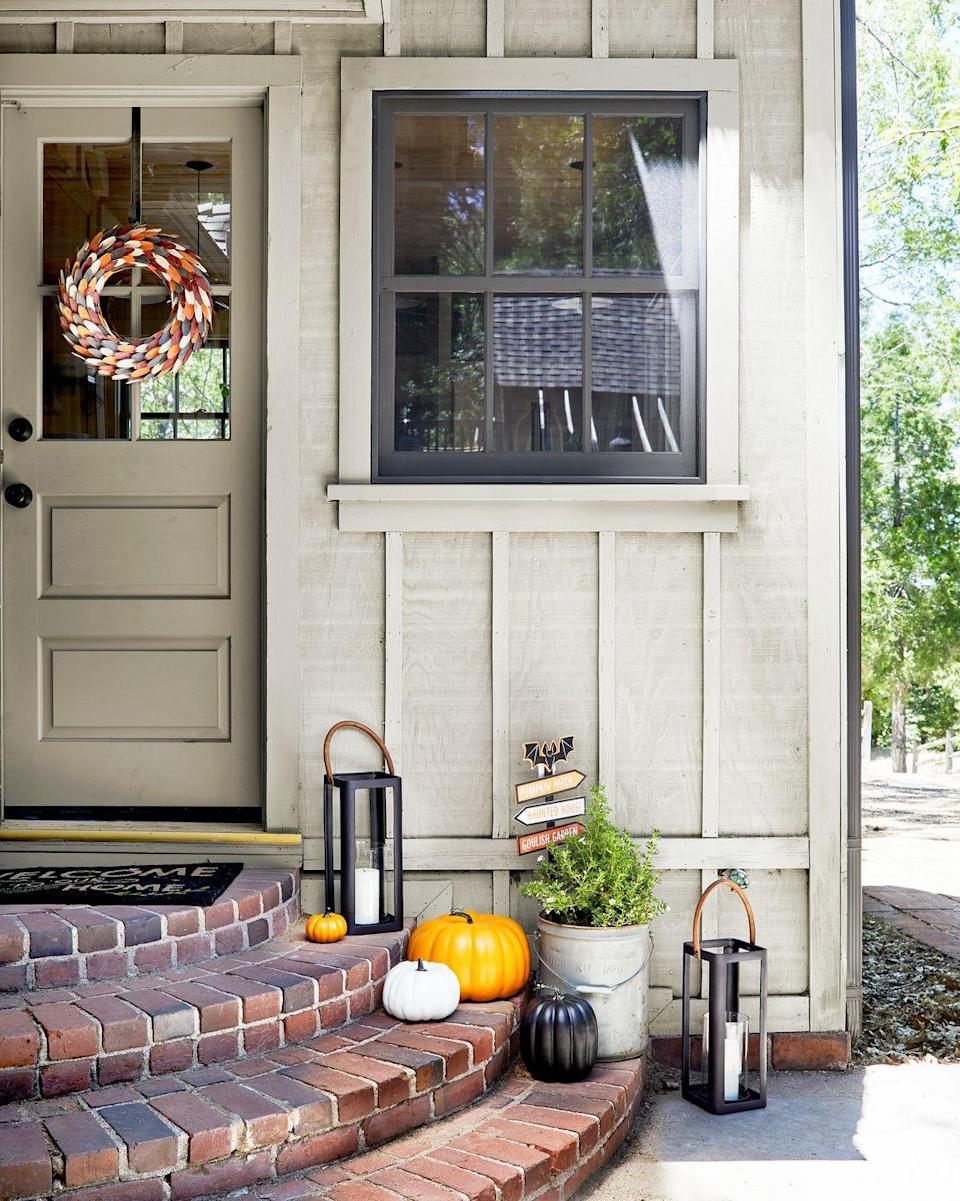 "<p>Line the steps on your front porch with pumpkins (paint one of them black to bring some darkness into the mix) and then make a mini Halloween-themed ""street sign"" to put in a pot of plants. Get the tutorial from <a href=""https://stylebyemilyhenderson.com/"" rel=""nofollow noopener"" target=""_blank"" data-ylk=""slk:Emily Henderson"" class=""link rapid-noclick-resp"">Emily Henderson</a>. </p>"