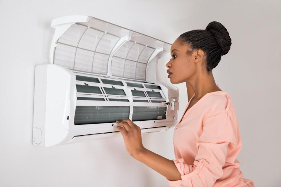 Woman Checking Air Conditioner At Home