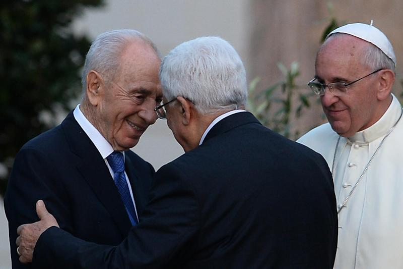 Israeli President Shimon Peres (left) shakes hands with Palestinian leader Mahmud Abbas as Pope Francis looks on following a peace summit at the Vatican, on June 8, 2014