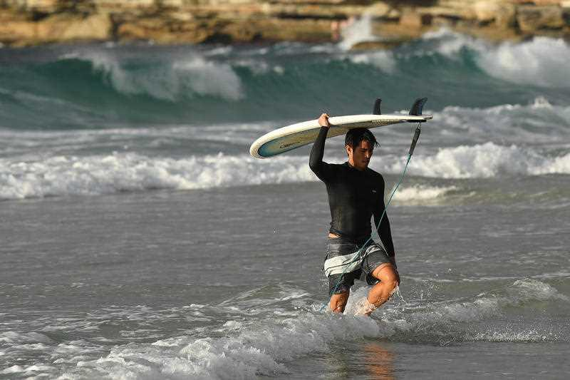 A surfer leaving the the water at Bondi Beach after it was reopened to the public.