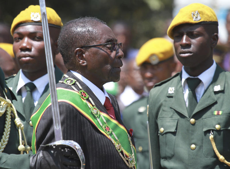 "FILE - In this file photo taken Tuesday, Sept. 17, 2013 Zimbabwean President Robert Mugabe inspects the guard of honor during the opening of the first session of the eighth Parliament of Zimbabwe in Harare. Zimbabwe's longtime President Robert Mugabe says he doesn't want anyone to be fooled by his impeccable Western style of dress and his precise, teacherly use of English: He is African through and through. ""I am not British, I am not a colonial product because I am a complete Zimbabwean, "" he told graduates at Great Zimbabwe University near the remains of the 13th Century walled city, for which Zimbabwe, the former colony of Rhodesia, is named. (AP Photo/Tsvangirayi Mukwazhi-file)"