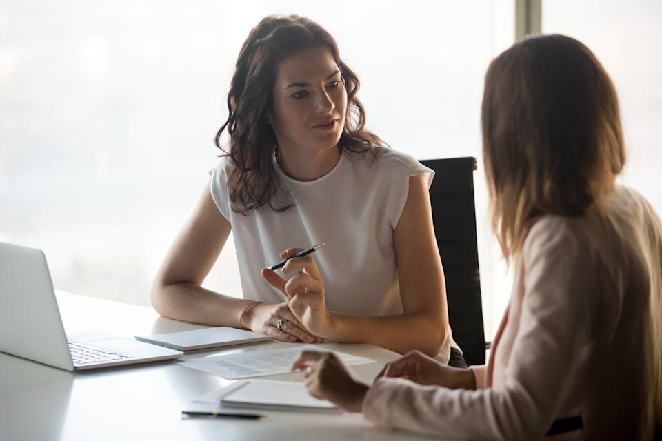 Two diverse serious businesswomen discussing business project working together in office, serious female advisor and client talking at meeting, focused executive colleagues brainstorm sharing ideas