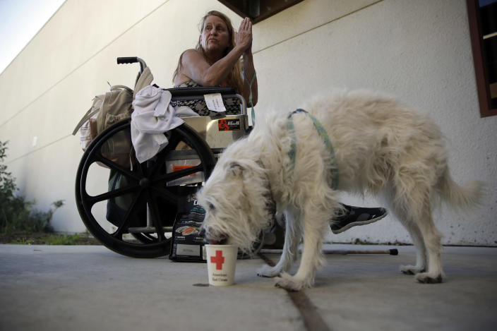 Mary, no last name given, sits on her wheelchair next to her dog Manny, outside of the gym at West Ranch High School after being evacuated from the Tick Fire Friday, Oct. 25, 2019, in Santa Clarita, Calif. (AP Photo/Marcio Jose Sanchez)