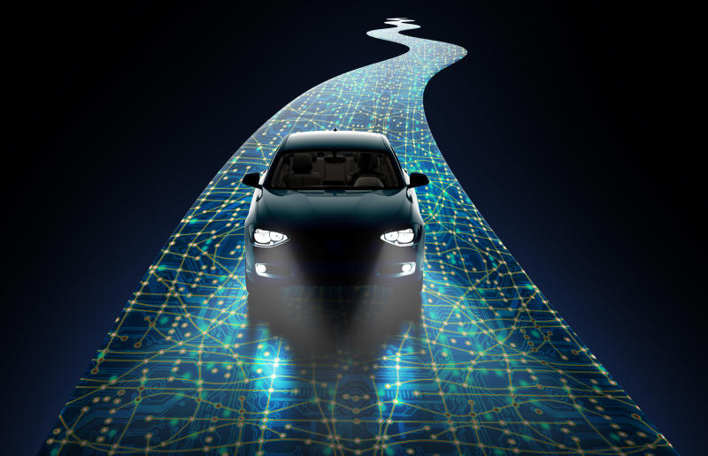 A car with headlights turned on driving along a path overlayed with bright computer circuit board lines.