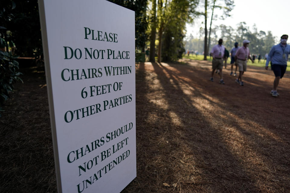 A sign posted on the course urges patrons to social distance during a practice round for the Masters golf tournament on Tuesday, April 6, 2021, in Augusta, Ga. (AP Photo/David J. Phillip)