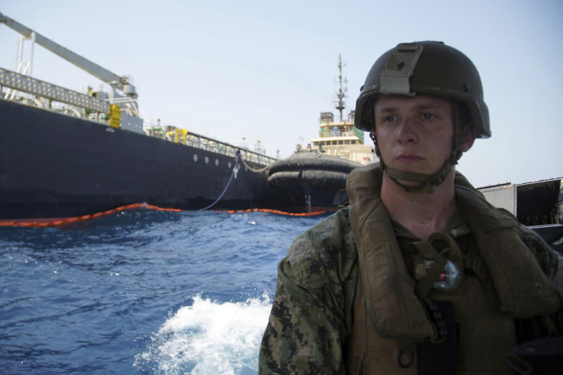 "The damaged Panama-flagged, Japanese owned oil tanker Kokuka Courageous, that the U.S. Navy says was damaged by a limpet mine, is seen behind a U.S. sailor, during a trip organized by the Navy for journalists, off Fujairah, United Arab Emirates, Wednesday, June 19, 2019. The limpet mines used to attack the oil tanker near the Strait of Hormuz bore ""a striking resemblance"" to similar mines displayed by Iran, a U.S. Navy explosives expert said Wednesday. Iran has denied being involved. (AP Photo/Fay Abuelgasim)"