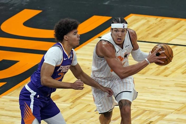 Orlando Magic forward Aaron Gordon, right, looks to pass as he is defended by Phoenix Suns forward Cameron Johnson
