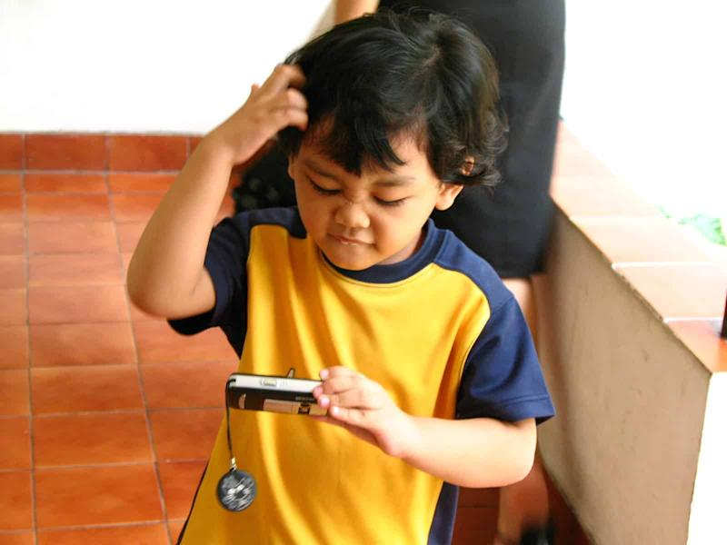 Small boy scratching his head looking at screen