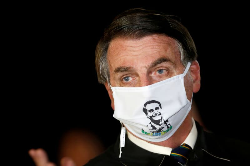 FILE PHOTO: Brazil's President Jair Bolsonaro speaks with journalists while wearing a protective face mask as he arrives at Alvorada Palace, amid the coronavirus disease (COVID-19) outbreak, in Brasilia