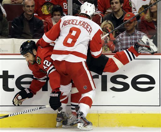 Chicago Blackhawks' Michal Rozsival (32) is checked by Detroit Red Wings' Justin Abdelkader (8) during the first period of Game 5 of the NHL hockey Stanley Cup playoffs Western Conference semifinals in Chicago, Saturday, May 25, 2013. (AP Photo/Nam Y. Huh)