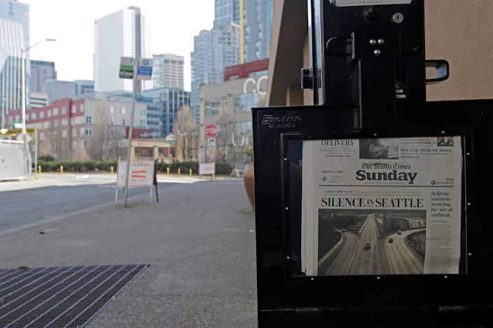 """A Seattle Times headline reading """"Silence in Seattle"""" eerily sits next to an empty street just outside the Times' newsroom."""