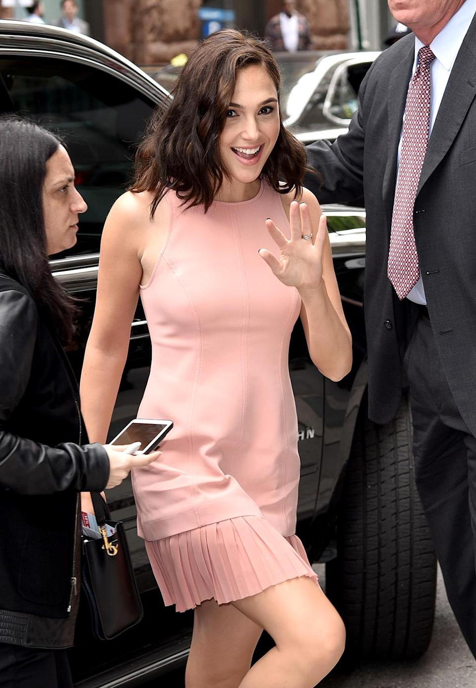 <p>Who says pink dresses have to be too sweet? Gadot looked sophisticated while rocking a pink frock with pleats as she arrived at the AOL Live offices in New York. (Photo: Derek Storm/Splash News) </p>