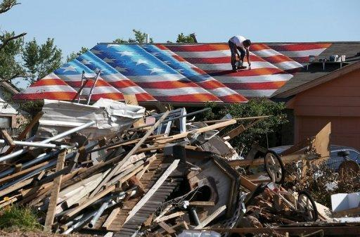 A man paints an American Flag on the roof of a home damaged by a tornado June 2, 2013 in Moore, Oklahoma. Three storm chasers were killed while pursuing the powerful tornadoes that tore through the US state of Oklahoma last week