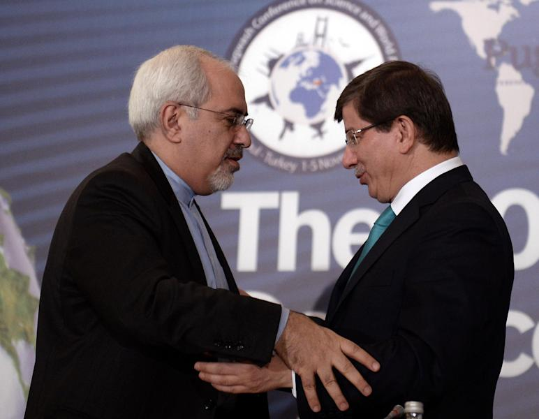 Iran's new Foreign Minister Mohammad Javad Zarif, left, and his Turkish counterpart Ahmet Davutoglu greet each other during a forum in Istanbul, Turkey, Friday, Nov. 1, 2013. Zarif said that both Iran and the West need a new approach if negotiations on Iran's nuclear program are to succeed. Speaking at a conference on disarmament in Istanbul, Zarif said that a decade of failed negotiations have led to consequences neither side wanted.(AP Photo)
