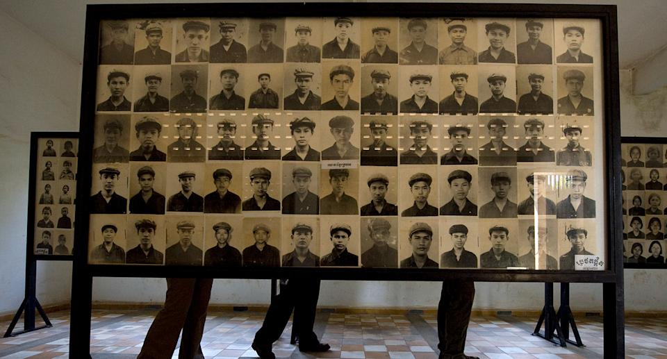 Tourists walk past hundreds of photographs of prisoners showcased in the classrooms of the Tuol Sleng Genocide Museum, also known as the notorious Security Prison 21 (S-21).