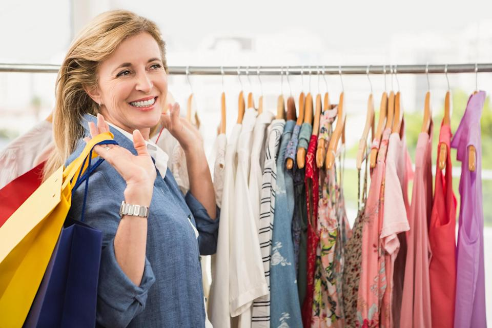 A smiling mature woman holding multiple shopping bags while looking at apparel.