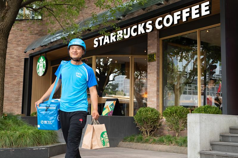 A delivery person carrying items out of a Starbucks cafe