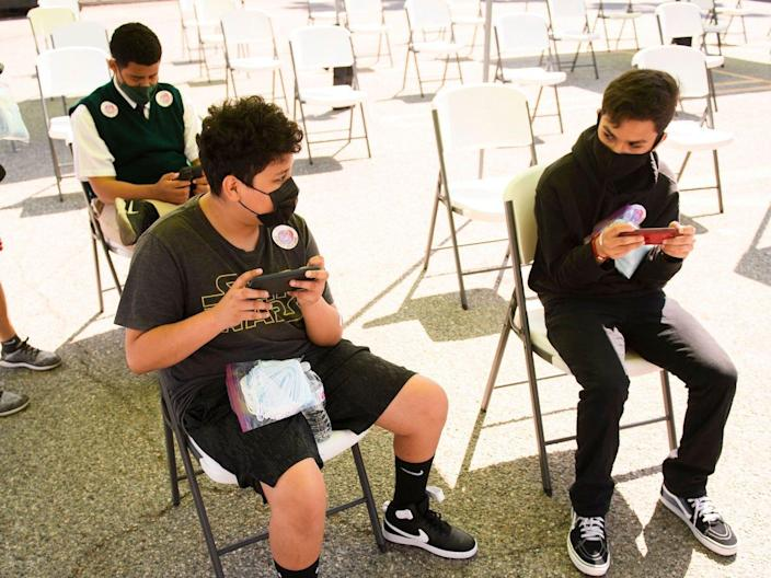 teenagers wait and play games after getting COVID-19 shots