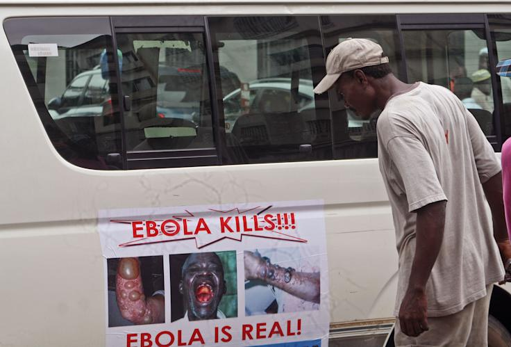 A man reads an Ebola warning on a van door in Monrovia, Liberia. (AP Photo/Abbas Dulleh)
