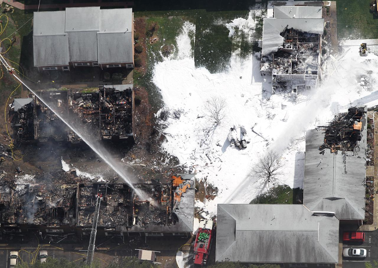 Emergency crews extinguish a fire at the scene of a jet crash Friday, April 6, 2012 in Virginia Beach, Va. Two Navy pilots ejected from a fighter jet Friday, sending the unmanned plane careening into a Virginia Beach apartment complex and tearing the roof off at least one building that was engulfed in flames, officials said. Six people, including both pilots, were taken to hospitals, officials said. The Navy said both aviators on board the jet ejected before it crashed around noon and were being taken to hospitals for observation. (AP Photo/Virginian-Pilot, Ross Taylor)