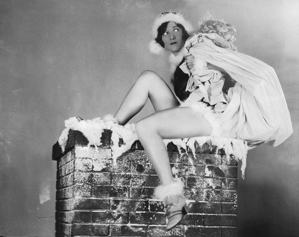 <p>Donning a Santa Claus costume, Crawford sits atop a chimney with a sackful of presents in 1926. </p>